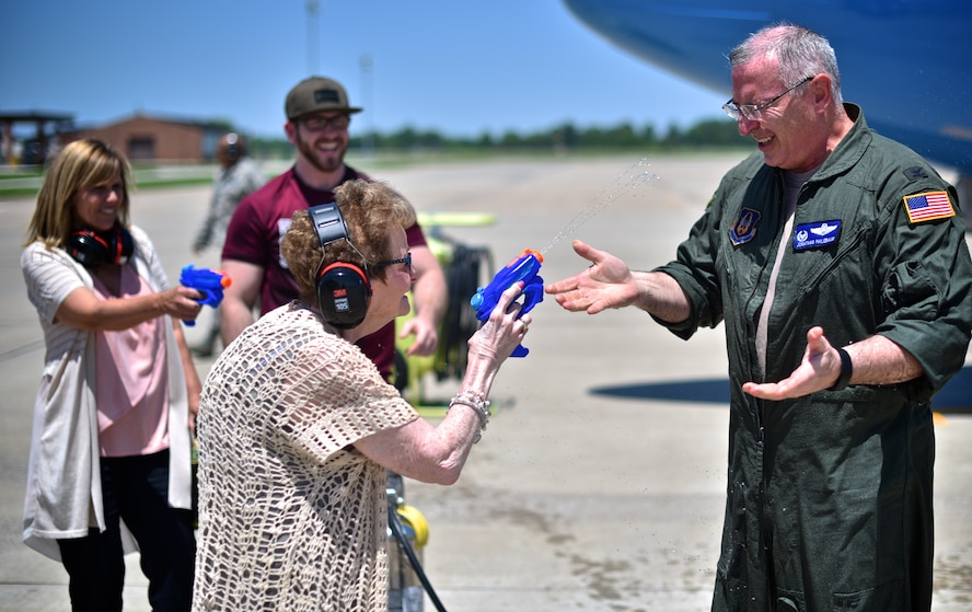 Rosalie Philebaum squirts water at her son, Col. Jonathan Philebaum, 932nd Airlift Wing commander, during his fini flight at Scott Air Force Base, Ill., May 31, 2017. Jonathan Philebaum's wife, JoAnn Philebaum, and their son both look on with delight as he is shocked by his mother's water blasts. (U.S. Air Force photo by Christopher Parr)