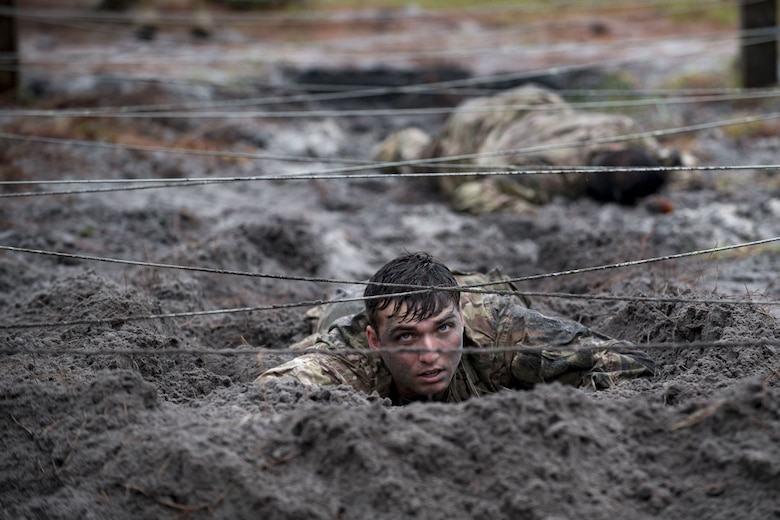Airmen from the 820th Base Defense Group low crawl through an obstacle during an Army Air Assault School readiness assessment, Dec. 7, 2017, at Camp Blanding, Fla. The AAA readiness assessment is designed to prepare Airmen for the course curriculum as well as its physical and mental stressors. During AAA, service members are taught an array of skills associated with rotary-winged aircraft, which improves the 820th BDG's ability to swiftly deploy and defend. (U.S. Air Force photo by Senior Airman Daniel Snider)