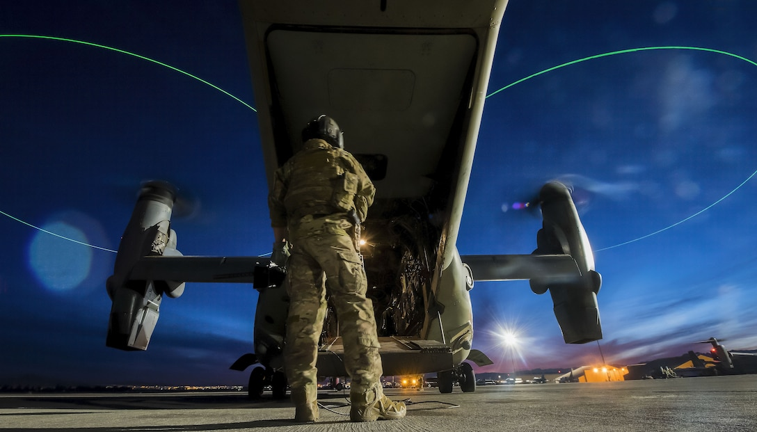 An Airman assigned to the 14th Weapons Squadron at Hurlburt Field, Fla., stands outside a CV-22 Osprey before a night mission during the U.S. Air Force Weapons School advanced integration course at Nellis Air Force Base, Nev., Dec. 10, 2017. The CV-22 is a tiltrotor aircraft that possesses vertical takeoff, hover and vertical landing qualities. (U.S. Air Force photo by Senior Airman Kevin Tanenbaum)
