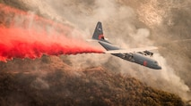 A C-130J Hercules assigned to the 146th Airlift Wing, Channel Islands Air National Guard Base, Port Hueneme, Calif., drops fire retardant chemicals onto a ridge line above Santa Barbara, Calif., Dec. 13, 2017, in an effort to contain the Thomas wildfire. (U.S. Air Force photo by J.M. Eddins Jr.)