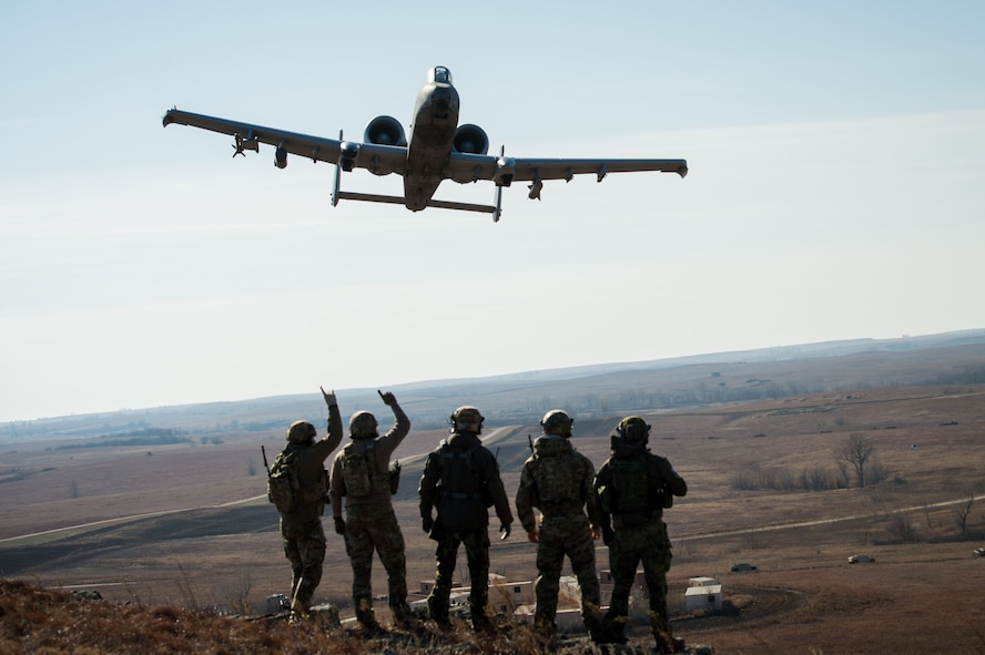 Members of the 146th Air Support Operations Squadron, from Oklahoma City, and Estonian tactical air control party specialists acknowledge a 442nd Fighter Wing A-10 Thunderbolt II from Whiteman Air Force Base, Mo., during a show of force after completing close air support training at Smoky Hill Air National Guard Range in Salina, Kan., Dec. 13, 2017. The Estonian TACPs traveled to the U.S. to work alongside members of the 146th ASOS to complete upgrade training and enhance multi-national relationships. This was the first time the 146th ASOS hosted the Estonian TACPs. (U.S. Air National Guard photo by Staff Sgt. Tyler Woodward)