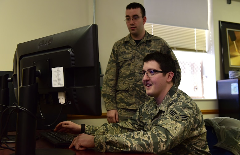 Senior Airman Erik Tatro, left, a programmer with the 595th Strategic Communications Squadron (SCS), and Senior Airman Gregory Salopek, also a programmer with the 595th SCS, sit at a computer in the 595th SCS offices at Offutt Air Force Base, Nebraska, January 12, 2018. Both Airmen participated in a DOD-Silicon Valley partnership in San Francisco in 2017, helping to create a program that would increase the efficiency of the aerial refueling scheduling process.