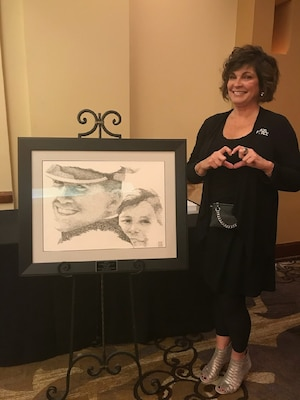 "Janine Sijan-Rozina forms a heart with her hands while standing next to a portrait of her and her brother, Capt.Lance Sijan. The portrait came from a screen capture of 8 mm footage of Sijan's Air Force Academy graduation. The artist, Charles Ingram, used the words ""thank you"" like brush strokes to create the image."