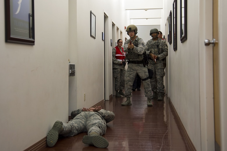 "Airmen assigned to the 6th Security Forces Squadron interact with a simulated ""victim"" during an active shooter exercise at MacDill Air Force Base, Fla., Jan. 9, 2017. This exercise served as an opportunity for law enforcement and first responders to train on faster and better ways to respond to an active shooter situation."