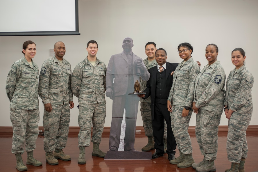 Members of the Dr. Martin Luther King Jr. committee and Anthony Brinkley, a retired chief master sergeant and inspirational speaker, pause for a photo with a display of King during an MLK observance luncheon at MacDill Air Force Base, Fla., Jan. 11, 2018.