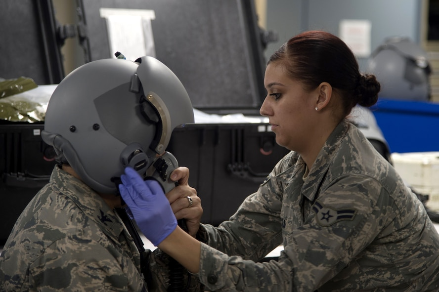 U.S. Air Force Airman 1st Class Taylor Garcia, right, an aircrew flight equipment apprentice assigned to the 6th Operations Support Squadron, performs a helmet fit test at MacDill Air Force Base, Fla., Jan. 11, 2017