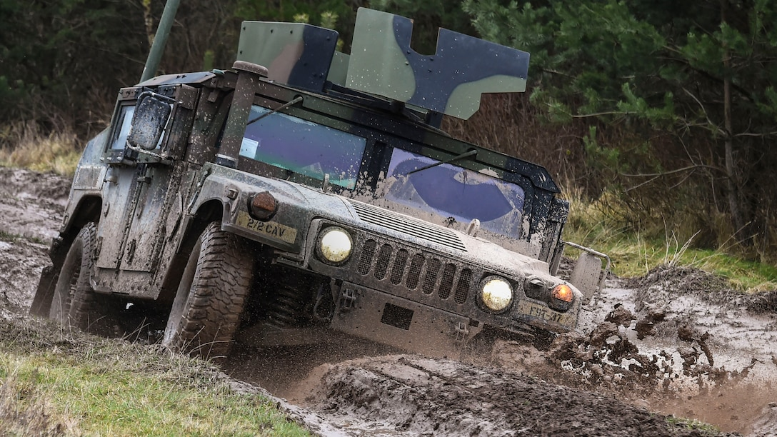 A camouflaged Humvee tilts and splashes up mud while driving on dirt roadway.
