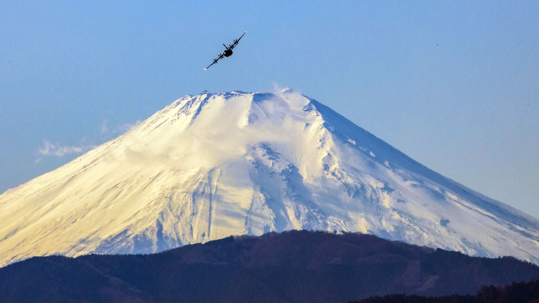 An aircraft flies above a giant snow-covered mountain.