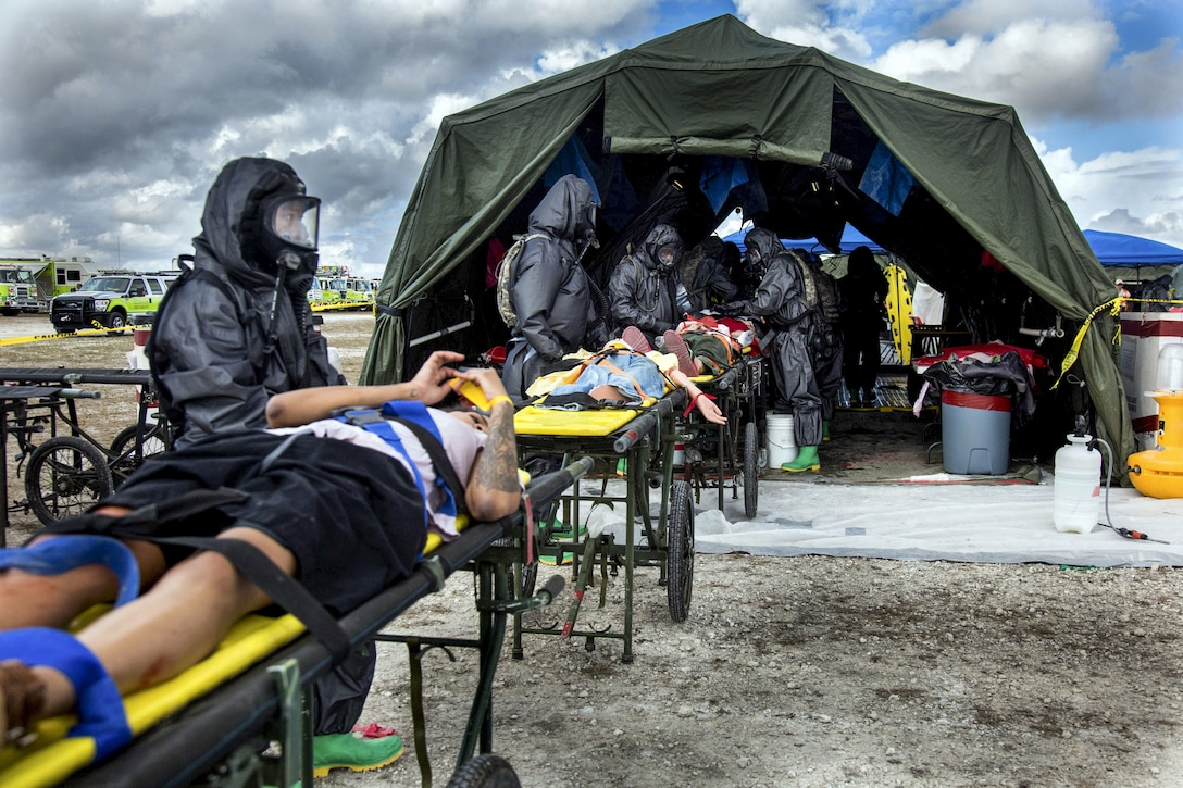Soldiers wearing full-body black protective suits and masks tend to mock patients on stretchers by a tent.
