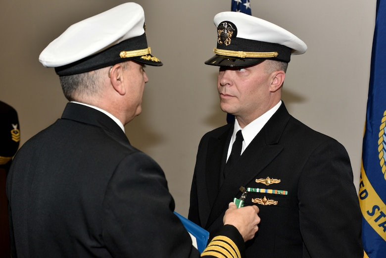 U.S. Navy Capt. William Lintz, Center for Information Warfare Training commanding officer, awards Lt. Cmdr. Christopher Allen, departing CIWT officer in charge, during the change of charge ceremony at the Event Center on Goodfellow Air Force Base, Texas, Jan. 12, 2018. Allen served as the CIWT Det. Goodfellow officer in charge from 2015 to 2018. (U.S. Air Force photo by Senior Airman Randall Moose/released)
