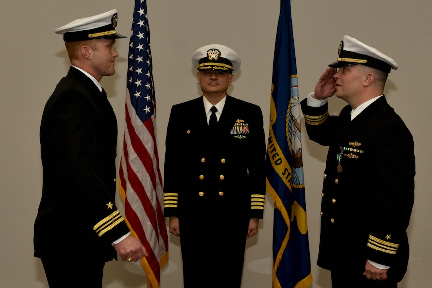 U.S Navy Lt. Cmdr. J. Austin Maxwell, Center for Information Warfare Training officer in charge, exchanges salutes with Capt. William Lintz, CIWT commanding officer, and Lt. Cmdr. Christopher Allen, departing CIWT officer in charge, during the change of charge ceremony at the Event Center on Goodfellow Air Force Base, Texas, Jan. 12, 2018. The change of charge ceremony is a time honored military tradition that signifies the orderly transfer of authority. (U.S. Air Force photo by Senior Airman Randall Moose/released)