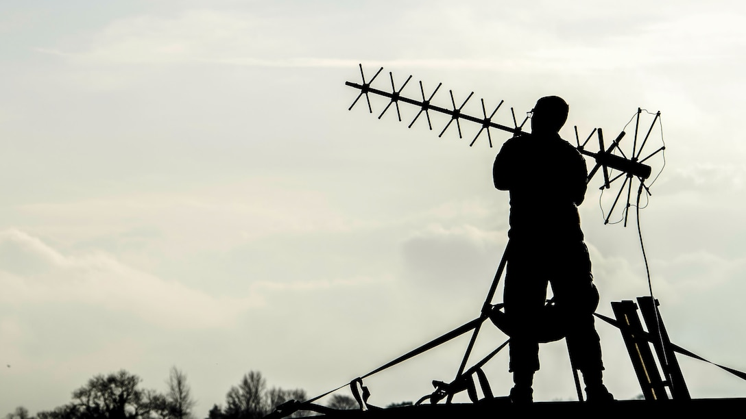 An airman, shown in silhouette, stands and adjusts an antenna.