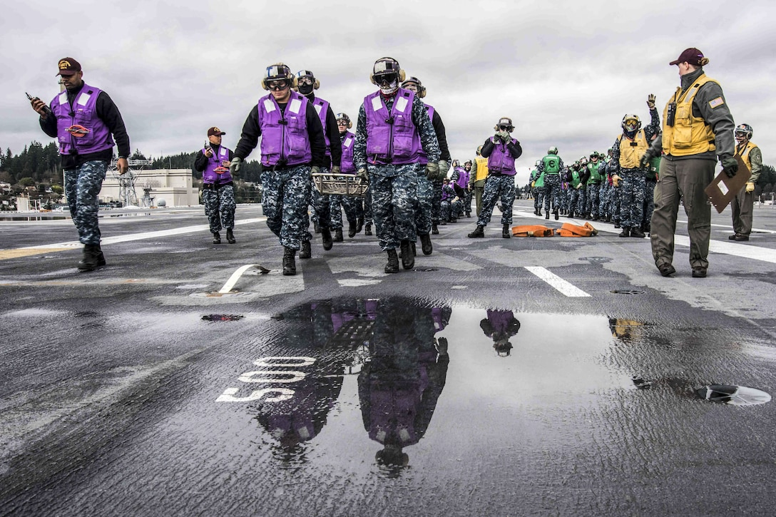 Sailors carry a stretcher on a flight deck.