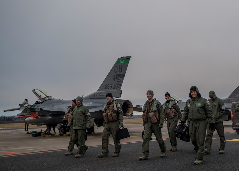 F-16 pilots from the 180th Fighter Wing, Ohio Air National Guard, walk toward the terminal at Amari Air Base, Estonia, Jan. 14, 2018. The pilots will fly missions in support of theater support packages. This TSP highlights the U.S.'s ability to deploy fighter aircraft in support of our partners and allies in the European theater, and around the world. (DoD photo by MC3 Cody Hendrix)