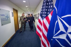 The chairman of the Joint Chiefs of Staff walks at NATO headquarters in Brussels.