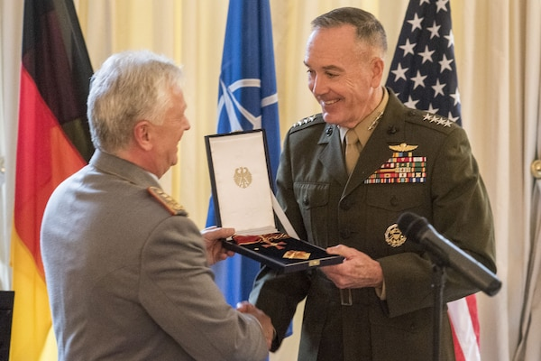Marine Corps Gen. Joe Dunford, chairman of the Joint Chiefs of Staff, receives the Knight Commander's Cross of Merit of the Federal Republic of Germany from Gen. Volker Wieker, his German counterpart, at the German Embassy in Brussels, Jan. 15, 2018. DoD photo by Navy Petty Officer 1st Class Dominique A. Pineiro
