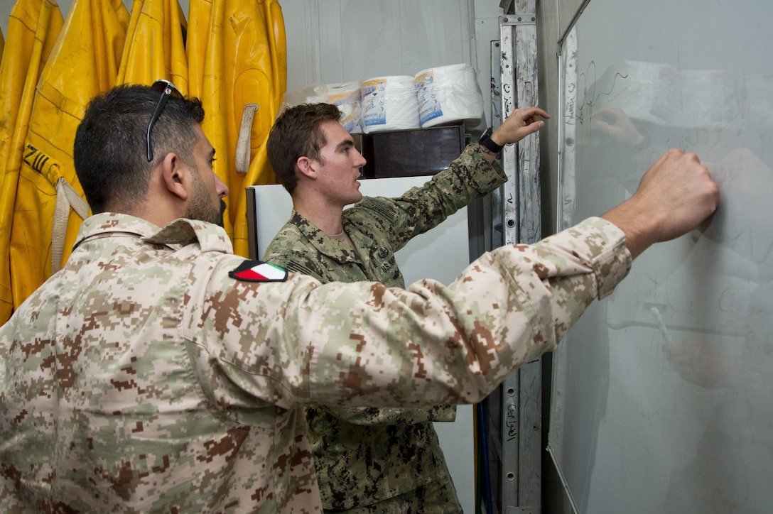 180107-N-XE158-0113 Mohammed Al-Ahmad Naval Base, (Jan. 7, 2018) Explosive Ordnance Disposal Technician 1st Class Kyle Hall, assigned to Commander, Task Group 56.1, exchanges sea mine procedures with a Kuwait Naval Force explosive ordnance disposal technician during a training evolution as part of exercise Eager Response 18. Eager Response 18 is a bilateral explosive ordnance disposal military exercise between the State of Kuwait and the United States. The exercise fortifies military-to-military relationships between the Kuwait Naval Force and U.S. Navy, advances the operational capabilities of Kuwaiti and U.S. forces to operate in the maritime domain, and enhances interoperability and warfighting readiness. (U.S. Navy photo by Mass Communication Specialist 1st Class Louis Rojas/Released)