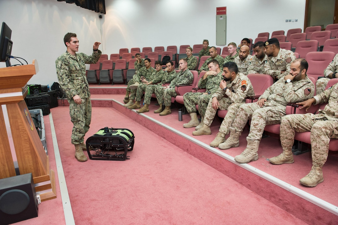 180107-N-XE158-0081 Mohammed Al-Ahmad Naval Base, KUWAIT (Jan. 7, 2018) Explosive Ordnance Disposal Technician 1st Class Kyle Hall, assigned to Commander, Task Group 56.1, explains the capabilities of the a remotely operated vehicle to Kuwait Naval Force explosive ordnance disposal technicians during a training evolution as part of exercise Eager Response 18. Eager Response 18 is a bilateral explosive ordnance disposal military exercise between the State of Kuwait and the United States. The exercise fortifies military-to-military relationships between the Kuwait Naval Force and U.S. Navy, advances the operational capabilities of Kuwaiti and U.S. forces to operate in the maritime domain, and enhances interoperability and warfighting readiness. (U.S. Navy photo by Mass Communication Specialist 1st Class Louis Rojas/Released)