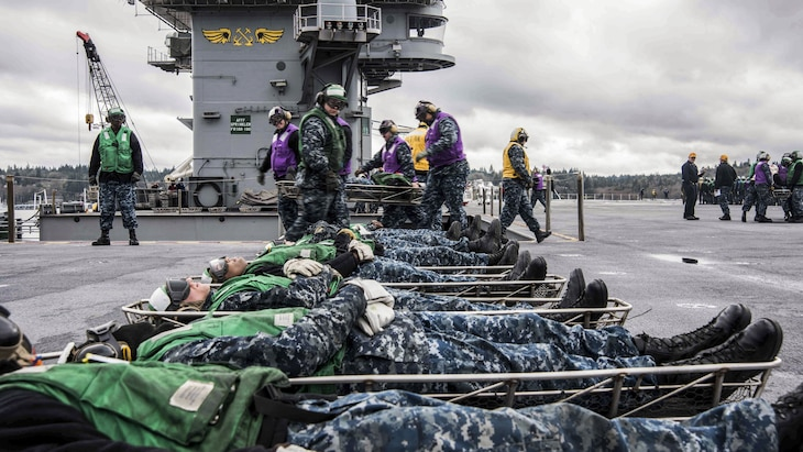 Sailors move simulated casualties during a firefighting and mass casualty drill
