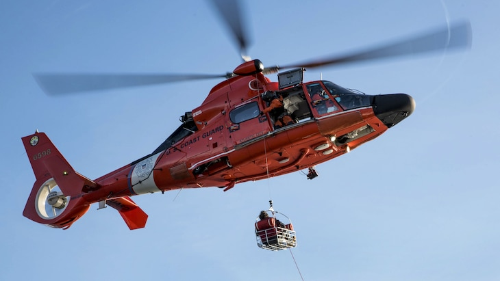 A rescue helicopter crew medevacs an ill fisherman as he rides in a basket attached to the helicopter.