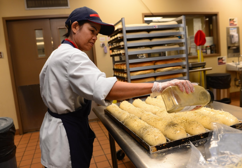 Jeranai Stolz, a deli chef assigned to the 28th Force Support Squadron, seasons loaves of bread inside the Raider Café at Ellsworth Air Force Base, S.D., Jan. 12, 2018.