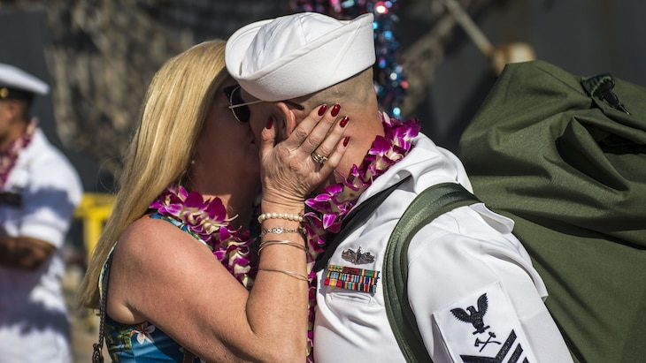 A sailor kisses his wife after returning from a deployment.