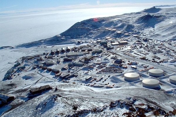 The National Science Foundation's McMurdo Station, as seen from the summit of Observation Hill, Antarctica. The station was established in December 1955 and is the logistics hub of the U.S. Antarctic Program, with a harbor, landing strips on sea ice and shelf ice, and a helicopter pad. Air Force photo