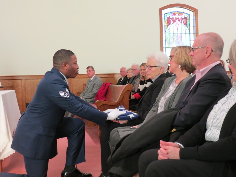 Staff Sgt. Mitchell Wright, 42nd Security Forces Squadron, presents the U.S. flag to Christine Weathington, widow of retired Chief Master Sgt. Billy Weathington, at the chief master sergeant's memorial service in Newville, Alabama, Jan. 13, 2018. Weathington, age 87 at his passing on Jan. 1, 2018, was the security forces career field's third chief master sergeant, ending his 27-year active duty career in 1979 as the senior enlisted advisor to Air Force Security Forces. He continued to serve as the director of Plans and Security Acquisitions, U.S. Air Force, retiring in 1990. Joining Wright in the 42nd SFS flag detail at the memorial service were Airman 1st Class Olivia Landry, Senior Airman Timothy Bridges and Senior Master Sgt. Jeffrey Tobin. (Courtesy photo)