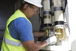 A contractor working with the Army Corps of Engineers in Puerto Rico ensures the fuel filter is working properly on a generator.