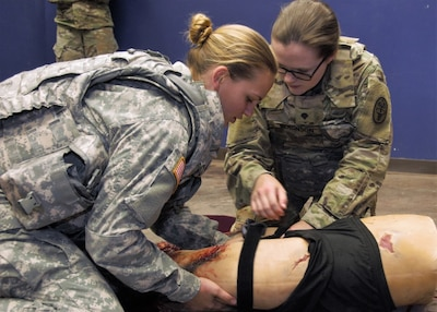 Combat medics at William Beaumont Army Medical Center's Inpatient Surgical Unit, apply a tourniquet to a simulated casualty during tactical combat casualty care training at the Medical Simulation Training Center at Fort Bliss, Texas.