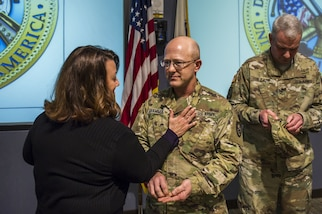 Lt. Col. Scott Grammer receives his new rank insignia from his wife, Stephanie Grammer, during his promotion ceremony to Colonel , January 11, 2017.