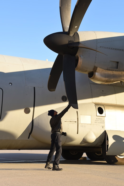 An Indian Air Force crew member manually rotates the propellers of a C-130 Hercules Jan. 13, 2018, after landing at Grand Forks Air Force Base, N.D. before heading to McChord AFB, Wash. for exercise Vajra Prahar. (U.S. Air Force photo by Airman 1st Class Elora J. Martinez)
