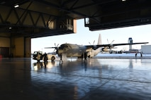 Grand Forks Airmen and service members with the Indian Air Force work together to tow a C-130 Hercules into a hangar Jan. 13, 2018, on Grand Forks Air Force Base, N.D. The Indian service members transited through Grand Forks AFB and received routine maintenance before heading to McChord AFB, Wash. for exercise Vajra Prahar. (U.S. Air Force photo by Airman 1st Class Elora J. Martinez)