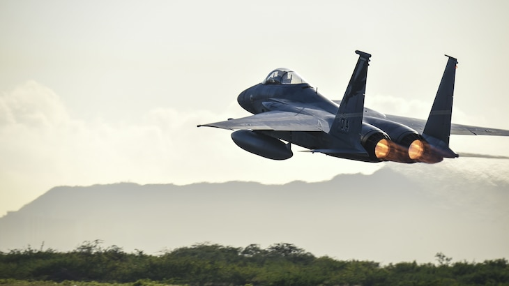 A fighter jet takes off with mountains in the background.