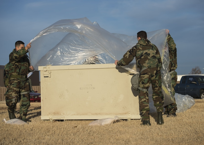 U.S. Air Force Airmen assigned to Altus Air Force Base, Okla., cover a storage unit with a tarp during an Ability to Survive and Operate (ATSO) exercise, Jan. 10, 2018, at Altus AFB.