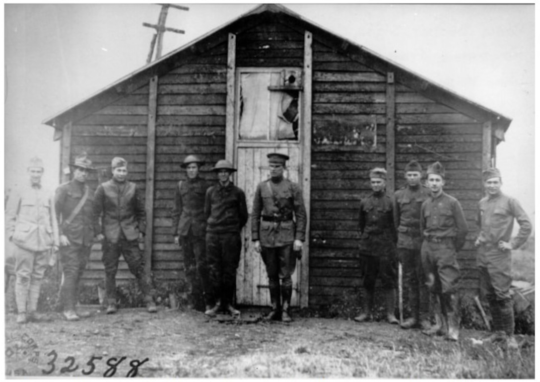 Soldiers stand in front of an aero intercept station.  These stations collected messages sent by enemy aircraft and alerted Allied forces to artillery movements or directed Allied pursuit squadrons.