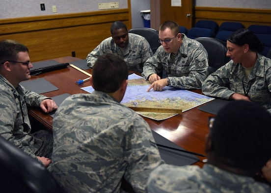 U.S. Air Force Airmen from the 325th Operations Support Squadron intelligence flight examine a map during an unclassified briefing at Tyndall Air Force Base, Fla., Oct. 25, 2017. The 325th OSS intel flight works behind the scenes analyzing and assessing information then disseminating the pertinent information to allow for better decision making. (U.S. Air Force photo by Airman 1st Class Isaiah J. Soliz/Released)