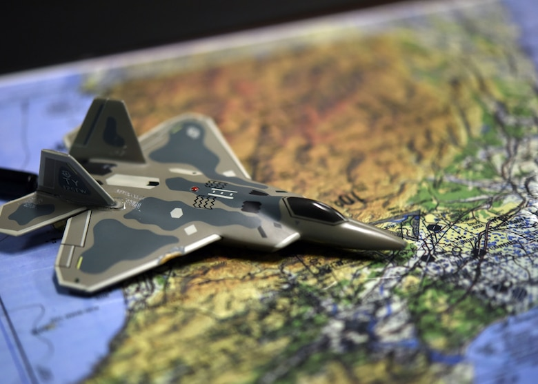 An F-22 Raptor model is shown on a map during an unclassified 325th Operations Support Squadron intelligence briefing at Tyndall Air Force Base, Fla., Oct. 25, 2017. The 325th OSS Intel flight works behind the scenes analyzing and assessing information then disseminating the pertinent information to allow for better decision making. (U.S. Air Force photo by Airman 1st Class Isaiah J. Soliz/Released)