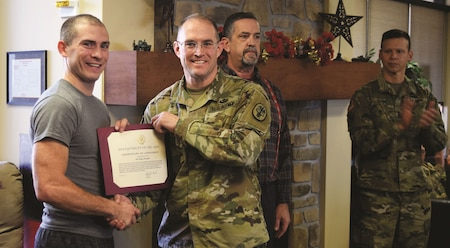 Lt. Col. Brady Beall, right, Warrior Transition Battalion commander, presents Staff Sgt. Shawn Runnells with a certificate of achievement for his excellence in athletic achievement Dec. 15 at the WTB Soldier Family Assistance Center. Runnells was recognized for his participation in wheelchair basketball, seated volleyball and air rifle events during the regional Warrior Games trials in Fort Benning, Georgia, in November.
