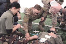 Cpl. Cedric Jackson, Troop C, 5th Squadron, 4th Cavalry Regiment, 2nd Armored Brigade Combat Team, 1st Infantry Division, assists a Hungarian soldier in applying tape to secure a fluid administration tube to a simulated casualty during a combat life saver course U.S. Soldiers led Dec 11-12.