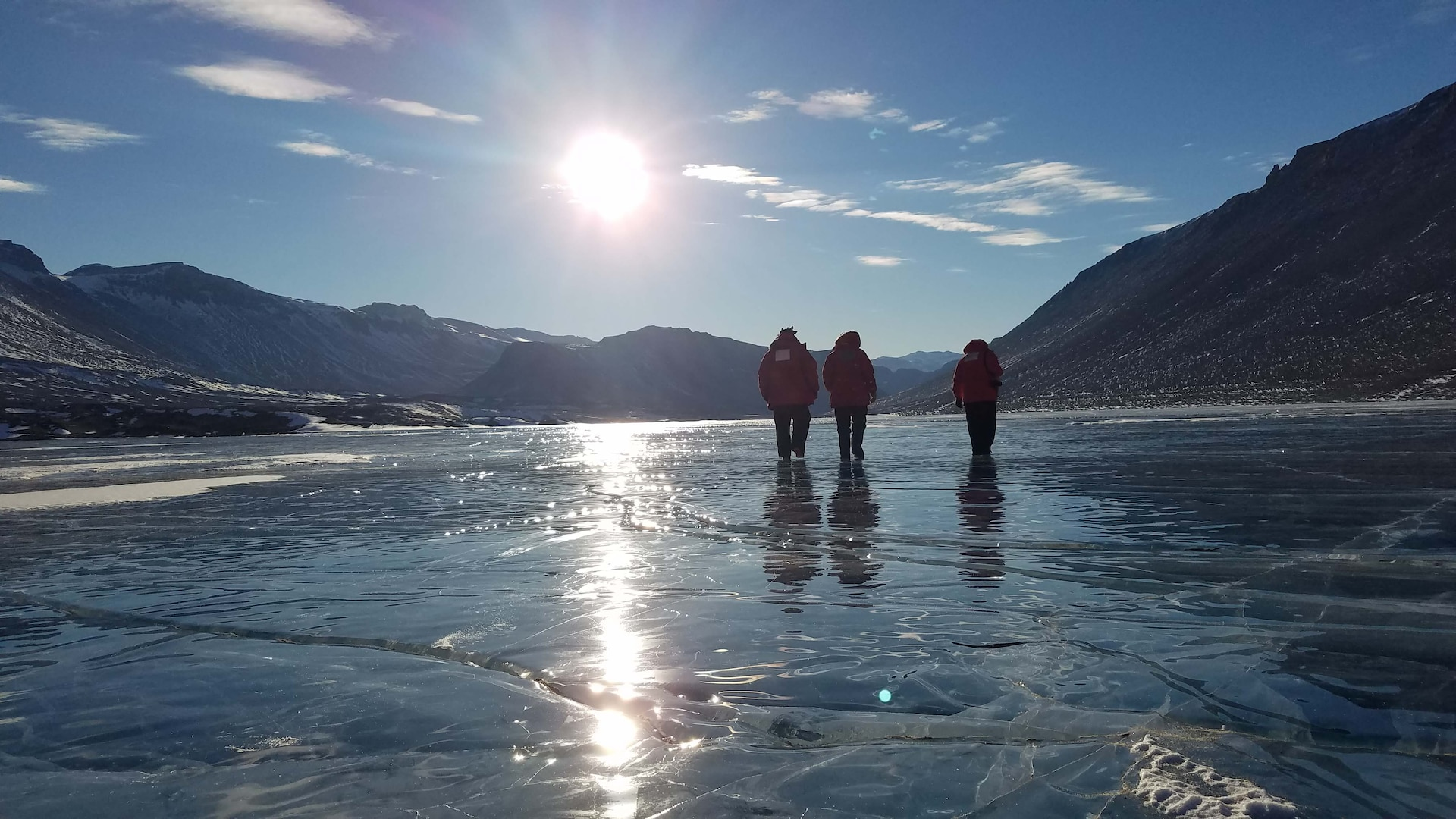 Airmen from the Air Force Technical Applications Center, Patrick AFB, Fla., walk on a frozen lake in Antarctica after a full day of performing maintenance on the center's seismic equipment near Bull Pass.  The photo, taken at about 10 p.m., illustrates the 24-hour daylight cycle at Earth's southernmost point.  Pictured from left to right:  Staff. Sgt. Jeremy Hannah, Senior Airman Andrew Pouncy and Staff Sgt. Justin Sherman.  (U.S. Air Force photo by Senior Airman Richard Westra)