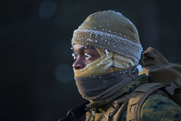 A Marine faces the cold as snow freezes to his eyelashes.