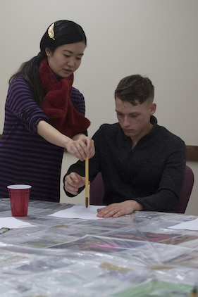 Students sit around a table practicing calligraphy