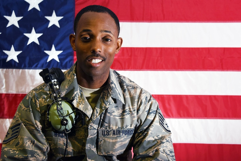 A service member poses for a headshot in front of a flag.