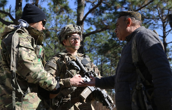 Afghan National Defense Security Forces role players talk to Capt. Justin Alexander, a combat team advisor team leader assigned to the 1st Security Force Assistance Brigade during a simulated event at the Joint Readiness Training Center at Fort Polk, La., Jan. 13, 2018. The JRTC rotation was conducted in order to prepare the newly formed 1st SFAB for an upcoming deployment to Afghanistan in the spring of 2018. SFAB's provide combat advising capability while enabling brigade combat teams to prepare for decisive action, improving readiness of the Army and its partners. (U.S. Army photo by Pfc. Zoe Garbarino/Released)
