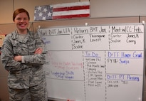 "Staff Sgt. Kaitlyn Kennedy, 932nd Development and Training Flight Coordinator, looks over her ""to do list"" Jan. 5, 2018, at Scott Air Force Base, Ill.  She stands proudly by her project board for the month of January, keeping track of Airmen as they come and go from orientation courses to basic training.  She also helps counsel two new trainees and assists the recruiting team in the headquarters building as needed.  (U.S. Air Force photo by Lt. Col. Stan Paregien)"