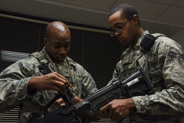 Staff Sgt. Jonathan Carthron (left) and Airman 1st Class Michael Brice, 4th Security Forces Squadron, clear a rifle in preparation for exercise Thunderdome 18-01, Jan. 11, 2018, at Seymour Johnson Air Force Base, North Carolina. After being issued a weapon, security forces personnel must visually inspect it to ensure it is in proper working order. (U.S. Air Force photo by Staff Sgt. Brittain Crolley)