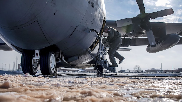 An airman inspects an aircraft surrounded in ice.