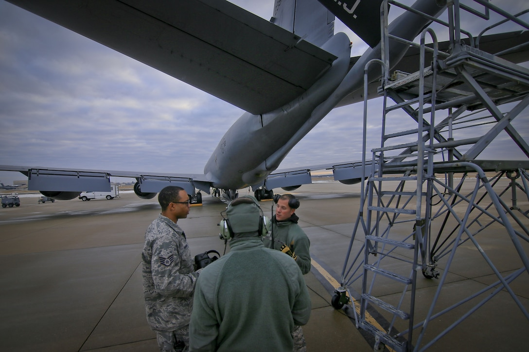 New Jersey Air National Guard Staff Sgt. Garion Reddick, left, an aircraft electronics specialist, talks with KC-135R crew chiefs Tech. Sgt. Raymond DeMarco, center, and Staff Sgt. Robert Cento, right, about a lighting issue on Joint Base McGuire-Dix-Lakehurst, N.J., Jan. 11, 2018. All three airmen are assigned to the 108th Wing. (U.S. Air National Guard photo by Master Sgt. Matt Hecht)