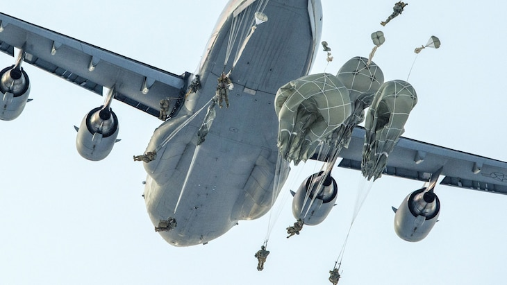 Soldiers with not-yet-open parachutes float around an aircraft in flight.